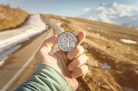 Compass in Hand mountain road background .Vintage Tone