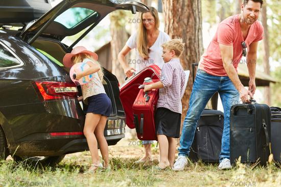Familie beim Koffer packen am Auto