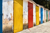 Several old wooden colorful doors on shabby light wall backgroun