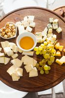 Cheese plate with hazelnuts, honey, grapes on wooden table