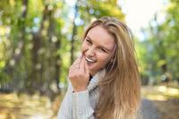 Happy blond girl posing in autumn park