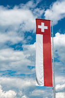 Swiss flag banner under an expressive blue sky with white cumulus clouds and copy space