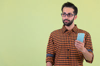 Young bearded Persian hipster man thinking while using phone