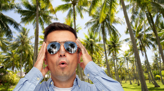 surprised man in sunglasses over tropical beach