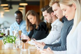 Handy-Sucht im Restaurant bei jungen Leuten