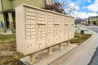 Residential mailboxes with numbered compartments on the side of a road
