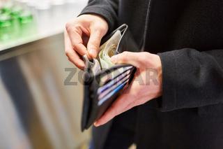 Mann beim Bezahlen mit Geldschein aus Brieftasche