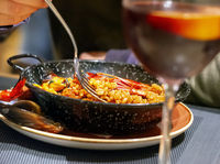 eating Valencian paella in a black pan using a fork