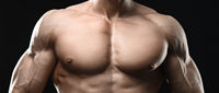 Perfect muscular male torso on black background