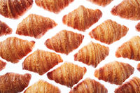 Pattern from freshly baked croissants on a white background.