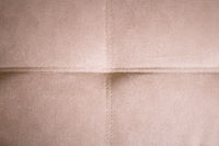 A close-up of a fragment of an expensive beige textile sofa in the room
