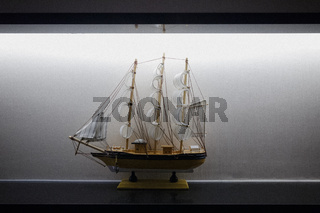 Model Sailboat Frigate Sitting on Display Shelf Lights Black White Elegant Decoration Centered