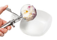 disher scoop with blueberry ice cream over bowl