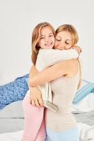 Mädchen im Schlafanzug umarmt liebevoll ihre Mutter