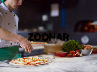 chef putting fresh vegetables on pizza dough