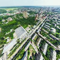 Aerial city view with crossroads and roads, houses, buildings, parks and parking lots. Sunny summer panoramic image