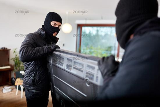Zwei Einbrecher tragen Fernseher als Beute