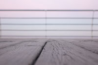 Wooden deck overlooking the sea sunrise with shallow depth of field.