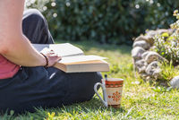 Person reads a book relaxed in the garden - rest while reading