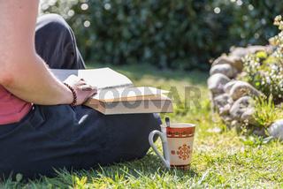 Person liest entspannt im Garten ein Buch - Erholung beim Lesen