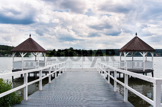 White roofed pier with wooden huts on lake, green forest and clouds in background, Poland