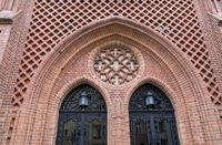 decorated entrance of an old church with red bricks