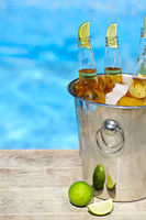 Closeup view of bucket with ice cubes, beer bottles and lime slices