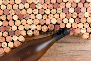 High angle shot of a group of wine corks and Chardonnay bottle on wood table with copy space