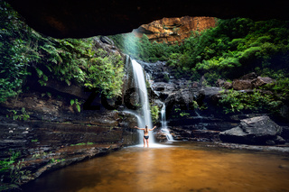 Woman cooling off in a mountain oasis and waterfall
