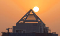 Sunrise behind the roof of skyscraper in Dubai