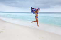 Woman in motion as she runs along the beach with Australian Flag.