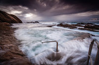 Turbulent ocean, big swell and surging rock pool overflows