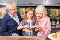 Großeltern und Mädchen beim Brot schmieren