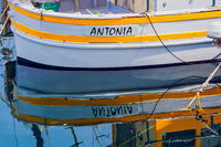Fishing boat is reflected in the water