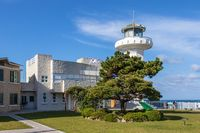 Main Ganjeolgot Lighthouse, upper direction light, with buildings and korean Flags near coast. Easternmost Point of Peninsula in Ulsan, South Korea. Asiaeasternmost, korea, peninsula, point, place