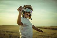 Happy boy at sunset playing at being aviator, he wears pilot glasses of airplanes and some cardboard like wings