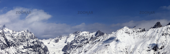Panorama of snowy mountains at sunny winter day