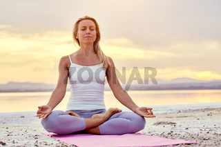 Middle-aged woman seated in lotus pose doing meditation on nature