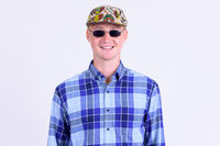 Happy young hipster man with sunglasses smiling