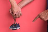 young pregnant couple holding newborn baby shoes