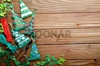 Handmade rustic green felt Christmas tree decorations and scissors flat lying on wooden table