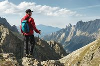 A bearded man in sunglasses and a cap with a backpack stands on top of a rock and looks into a rocky valley high in the mountains. The concept of tourism and easy trekking in the mountains outdoor