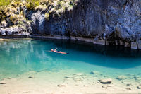 Female floating in natural blue pools