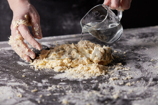 The baker kneads the dough for baking on a dark kitchen table.