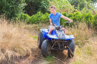 Teenage boy driving quad through curve