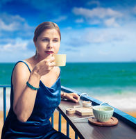 Beautiful woman enjoying tea on cafe terrace at seaside