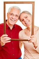 Senioren Paar schaut durch leeren Bilderrahmen