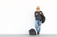 Fashionable young woman using her mobile phone while standing and waiting against plain white wall on the station whit travel bag by her side.