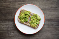 two slices of avocado toast on a plate on rustic wooden table