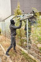 Fahrraddiebe heben Fahrrad über Zaun